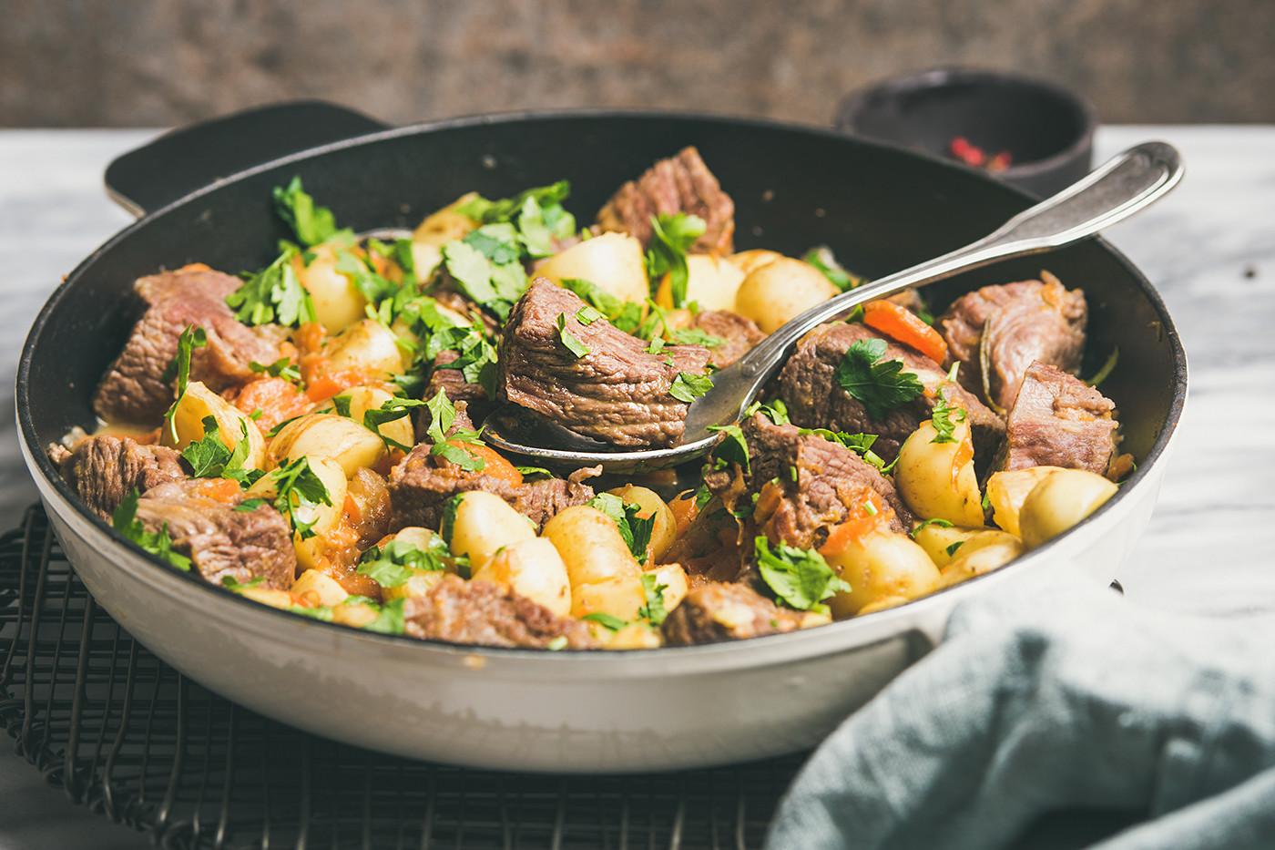 Braised beef meat stew with fresh parsley in pan