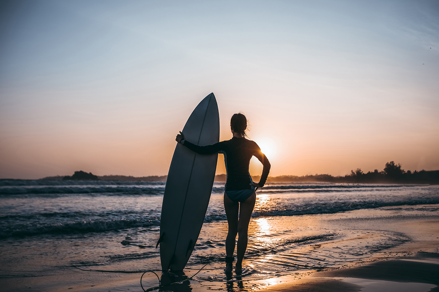Woman surfer with surfboard ready to surf on a beach