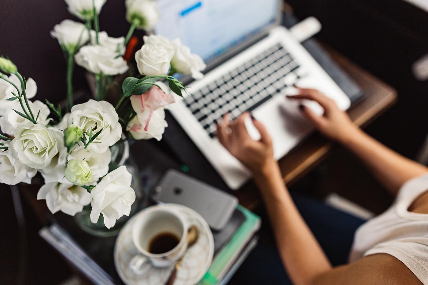 Woman working on laptop near flowers
